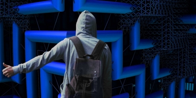 back of person in a grey hoodie, with a backpack, standing in a futuristic blue maze and holding out their thumb