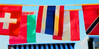 An assortment of small European flags hanging down from a string that connects them
