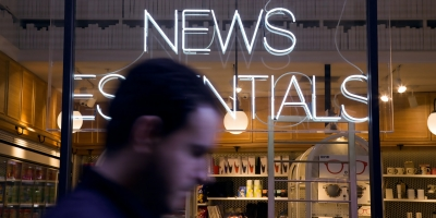 The top of a man's head walking past a shop with a neon sign that reads news essentials